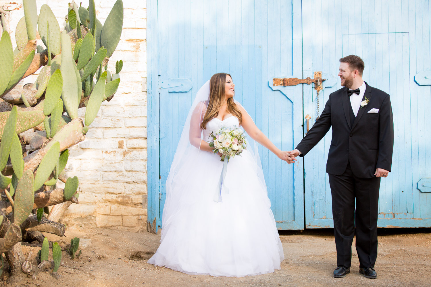Bride and groom portrait in front of the blue barn doors at Leo Carrillo