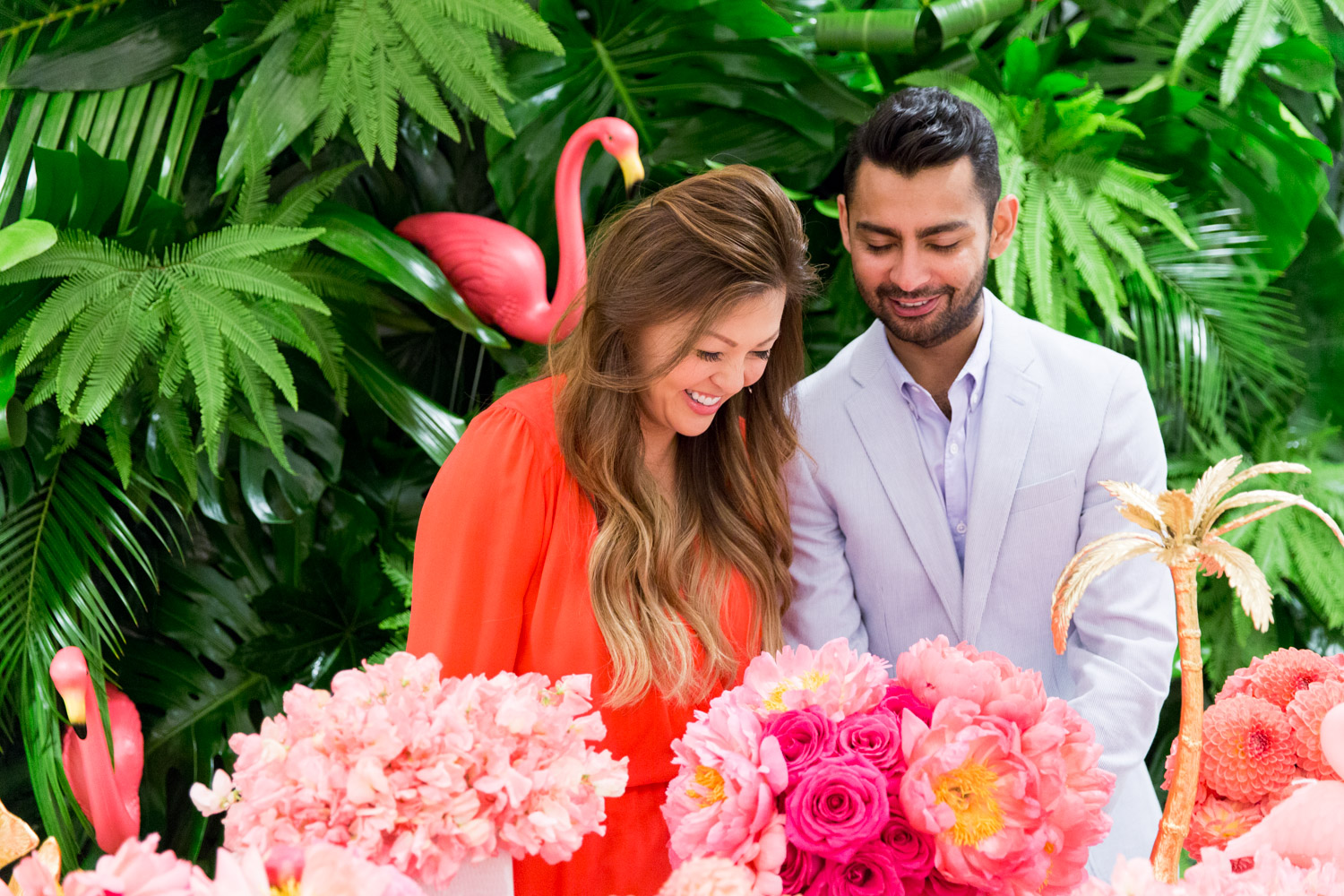 Jeannie Savage from Details Details and Fayaz from Bloom Box laughing and designing a Crystal and gold-plated pineapple and a gorgeous pink and orange floral arrangements with a green palm leaf wall and pink Kate Spade placemats with Bloom Box Details Details and Cavin Elizabeth Photography