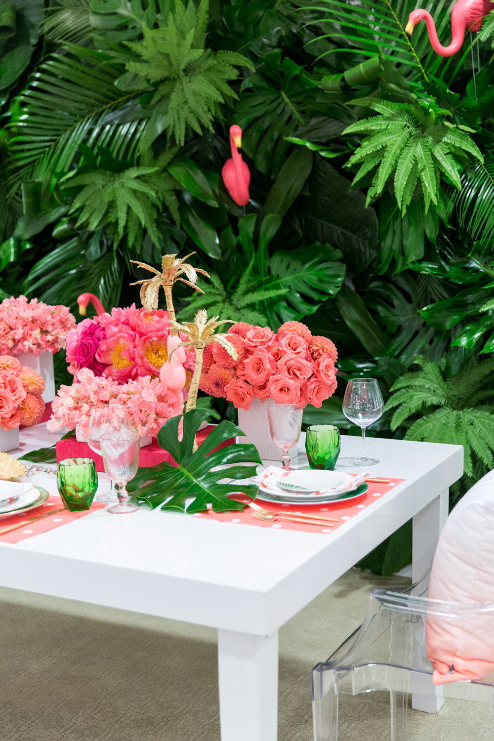 Gorgeous pink and orange floral arrangements with a green palm leaf wall and pink Kate Spade placemats with Bloom Box Details Details and Cavin Elizabeth Photography