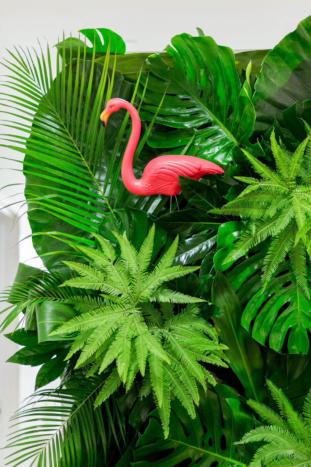 Green floral palm leaf wall with a pink flamingo as a table backdrop Gorgeous pink and orange floral arrangements with a green palm leaf wall and pink Kate Spade placemats with Bloom Box Details Details and Cavin Elizabeth Photography
