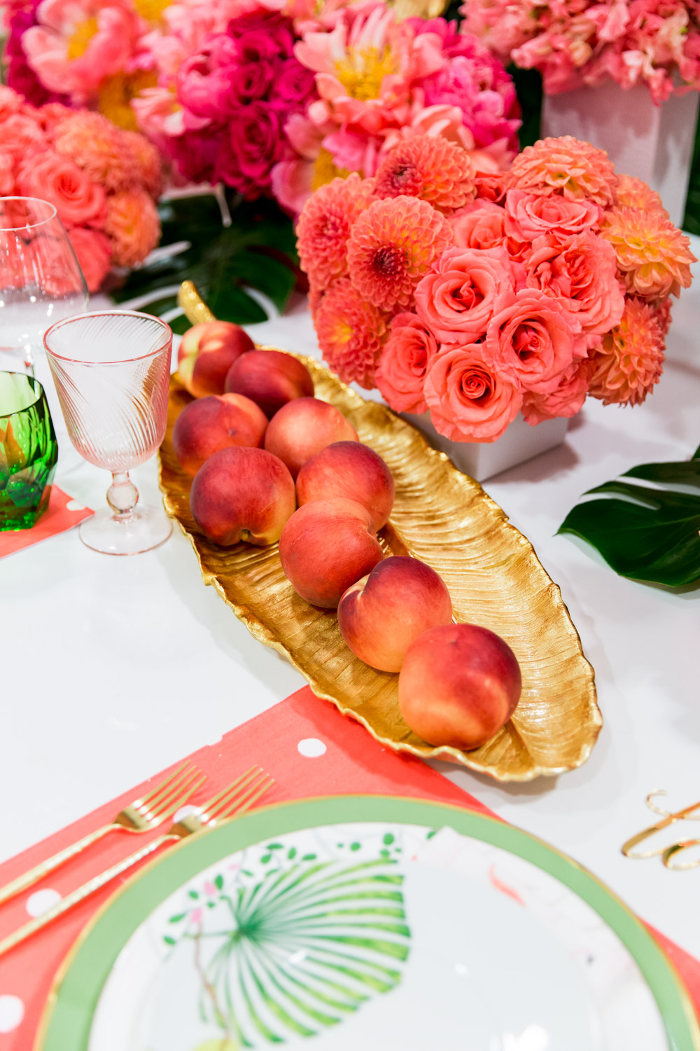 Peaches on a gold leaf bread plate on a luxury dinner party or wedding table Gorgeous pink and orange floral arrangements with a green palm leaf wall and pink Kate Spade placemats with Bloom Box Details Details and Cavin Elizabeth Photography
