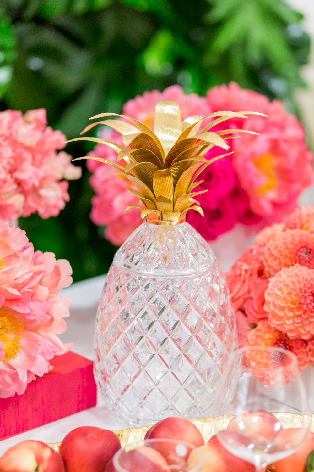 Crystal and gold-plated pineapple and a gorgeous pink and orange floral arrangements with a green palm leaf wall and pink Kate Spade placemats with Bloom Box Details Details and Cavin Elizabeth Photography