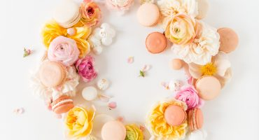 Gorgeous styled food photography with pink peach yellow and white flowers and macarons by Hey There Cupcake