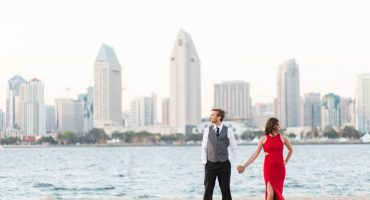 Engagement formal clothing ideas, red engagement session dress and a 3 piece suit and tie, intimate Coronado engagement photos with the San Diego city skyline in the background, Cavin Elizabeth Photography