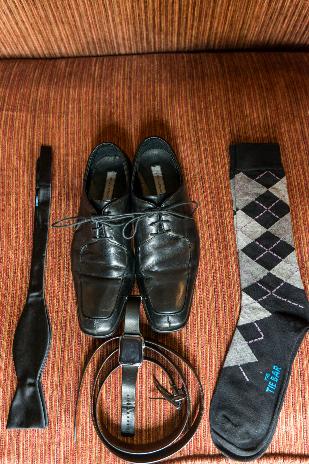Groom's wedding details with shoes, watch, bowtie, and socks