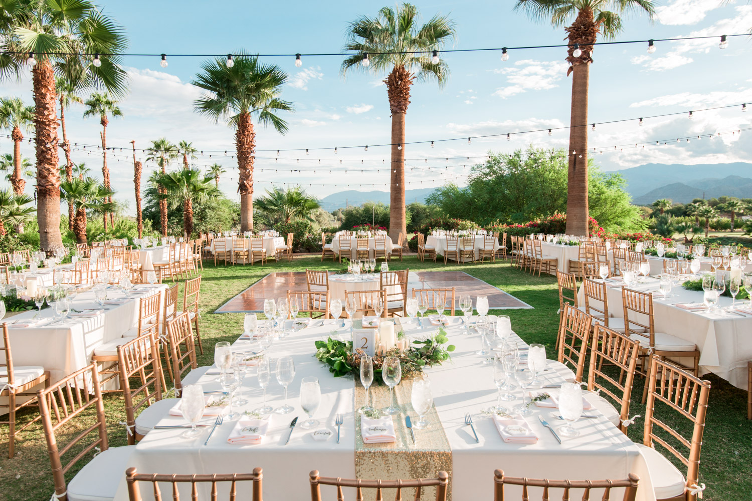 Luxury Palm Desert wedding reception with square and rectangle tables with white rose gold and green decor surrounded by palm trees, Cavin Elizabeth Photography