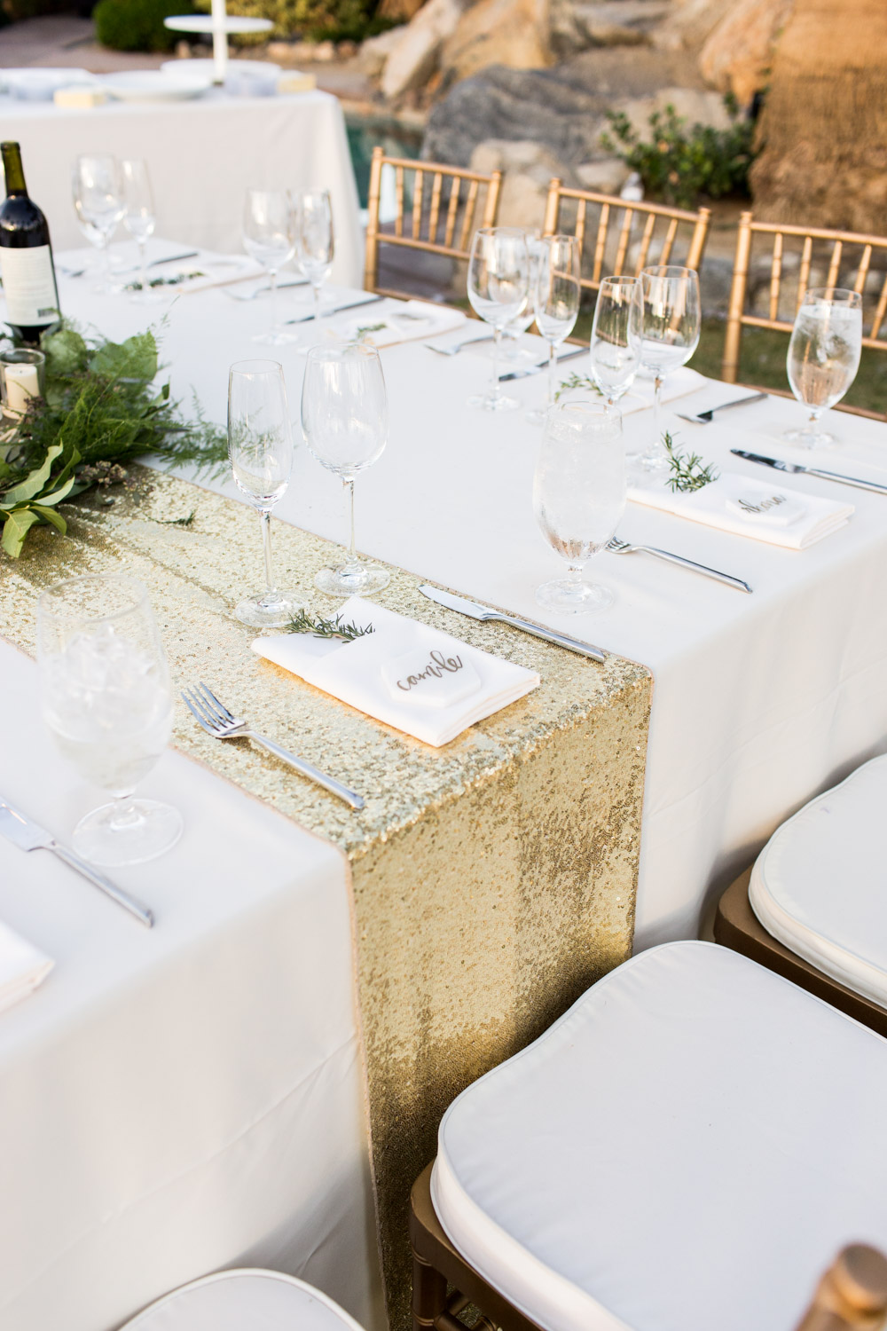 White linens with rose gold sequin table runner and blush napkin with rosemary sprig and hexagon marble place card, Cavin Elizabeth Photography