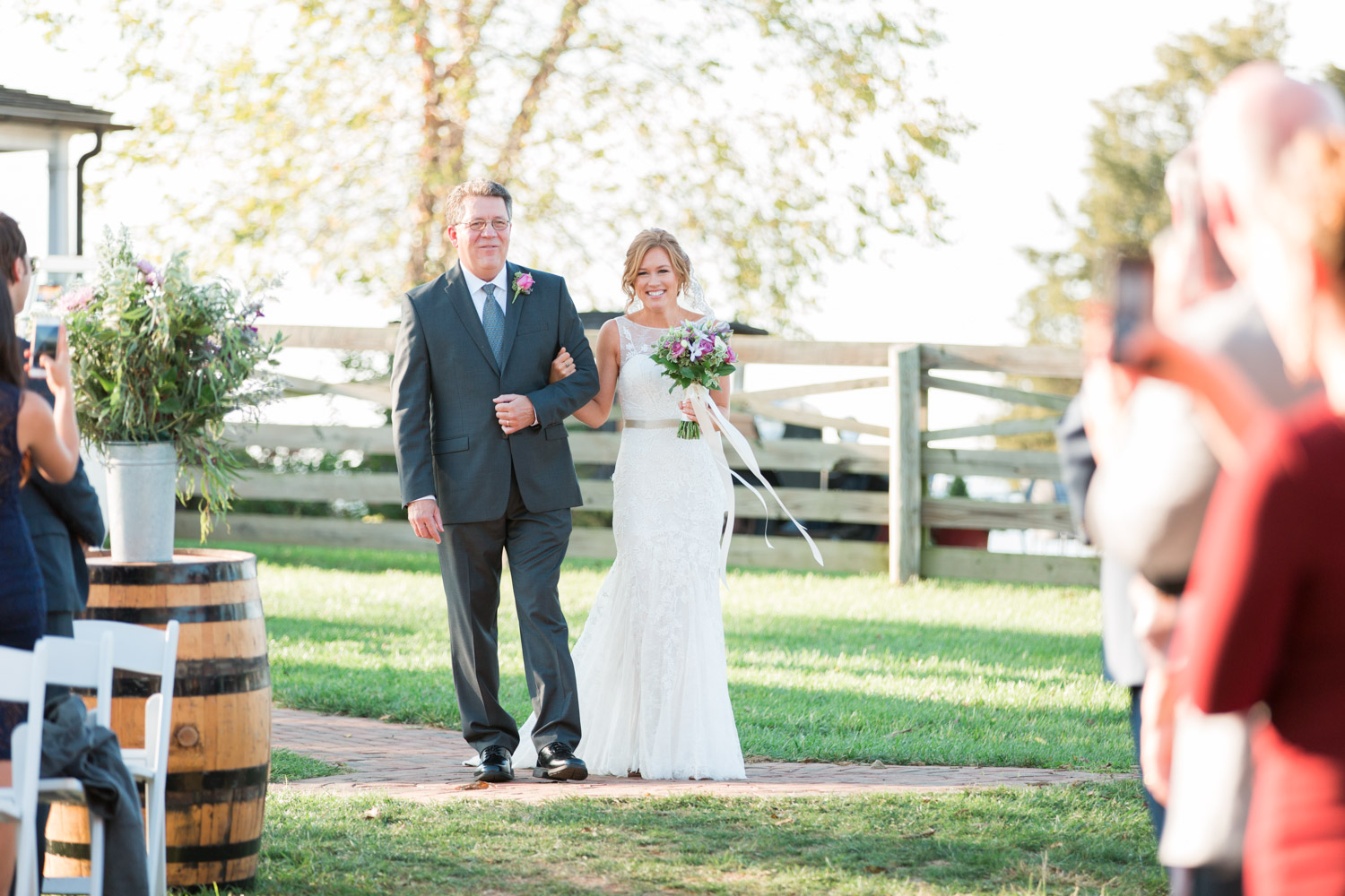Bride and father walking down the aisle at her wedding ceremony at Walker's Overlook under a large tree, garden wedding, Cavin Elizabeth Photography