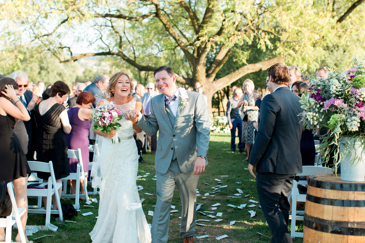 Bride and groom during money throw walking down the aisle at her wedding ceremony at Walker's Overlook under a large tree, garden wedding, Cavin Elizabeth Photography