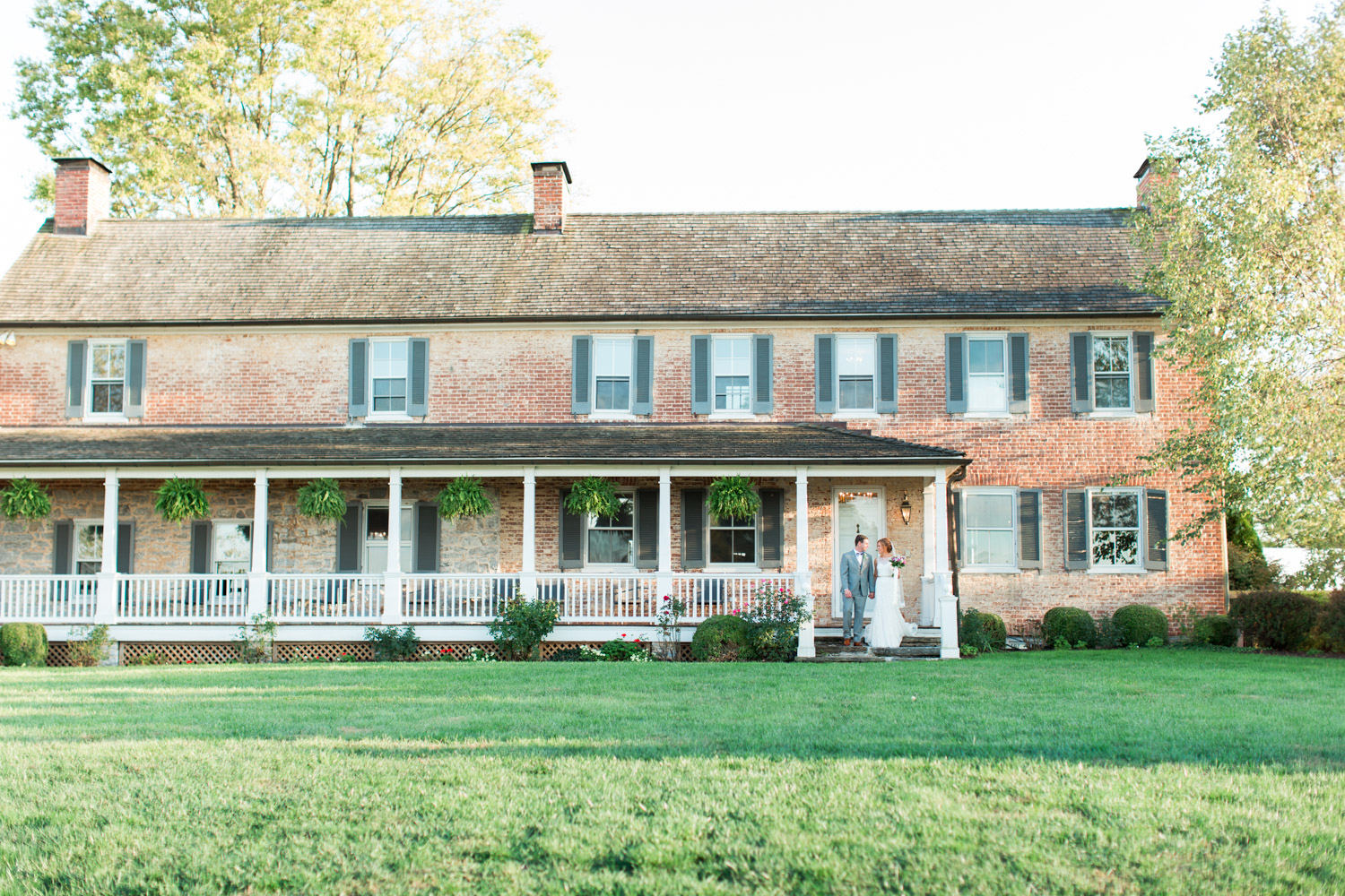 Bride and groom wide shot portrait in front of their venue in Maryland, Cavin Elizabeth Photography