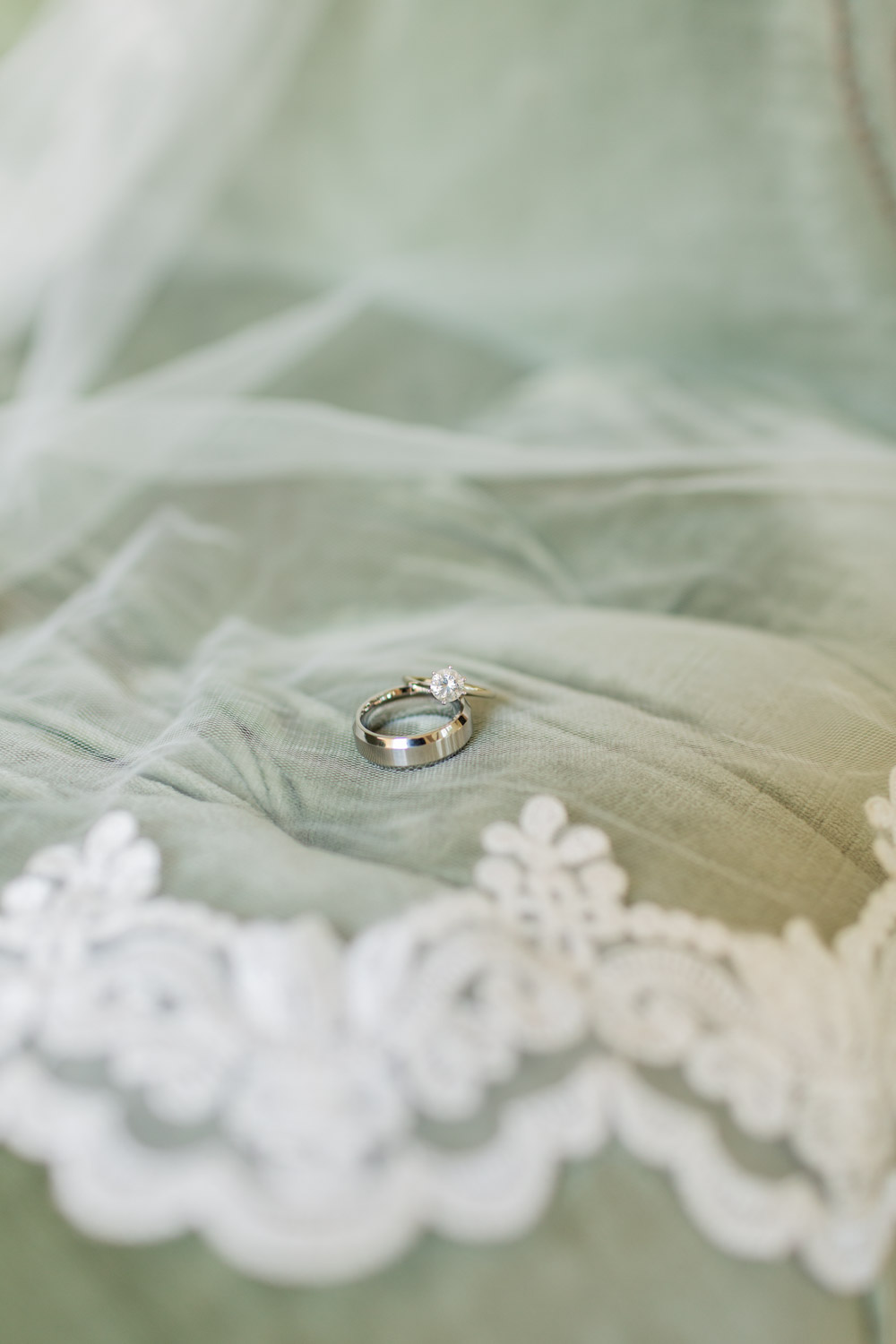 Round solitaire engagement ring and platinum men's wedding band on top of a lace veil, Cavin Elizabeth Photography