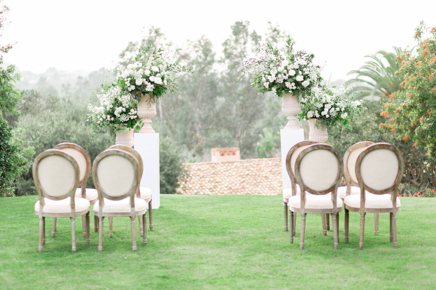 Rancho Valencia Wedding Photography by Cavin Elizabeth, wedding ceremony with gorgeous neutral chairs and large floral arrangements of white and green