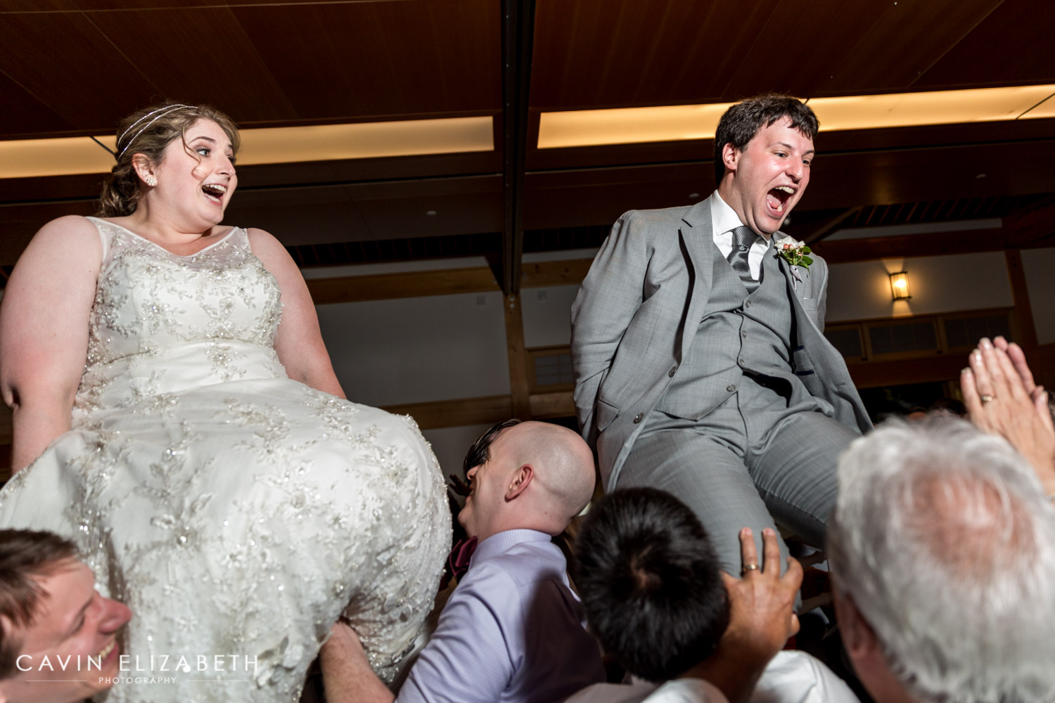 Jewish Wedding Hora, bride and groom laughing and screaming during their wedding horah, fun wedding reception candid photo