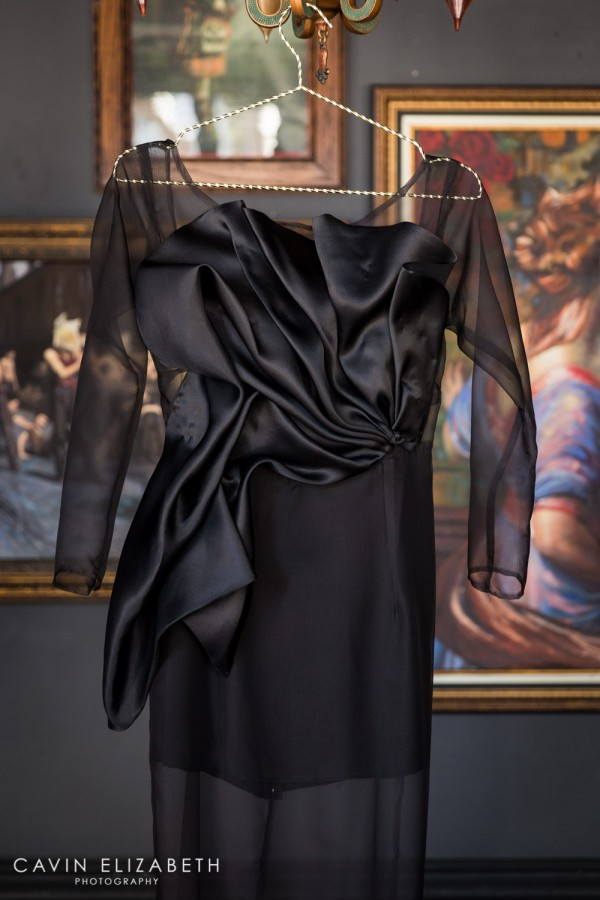 Black couture wedding gown by Paolo Corona Paris with sheer sleeves and a big silk bow