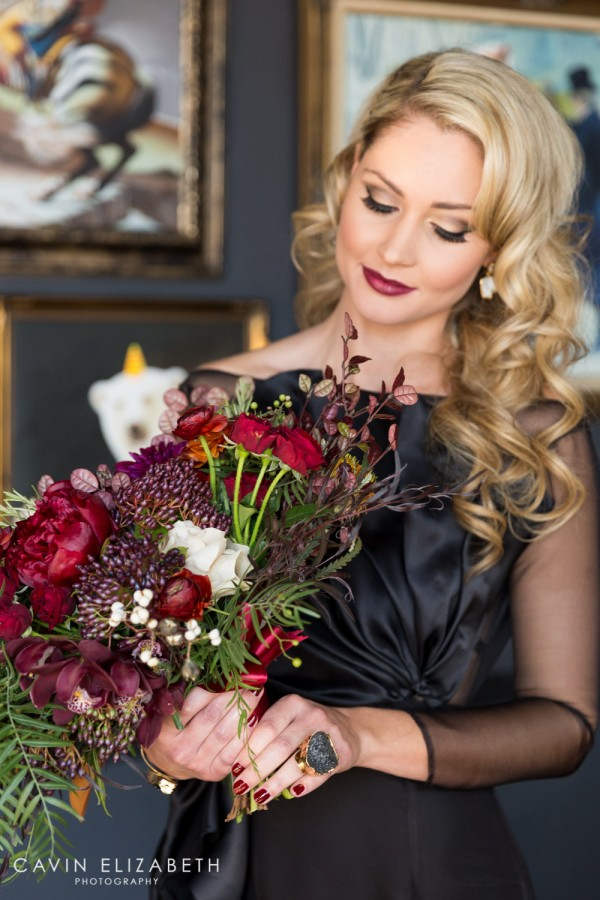 Bride wearing a black Paolo Corona Paris dress with a red purple green and blush bouquet by Blooms by Breesa