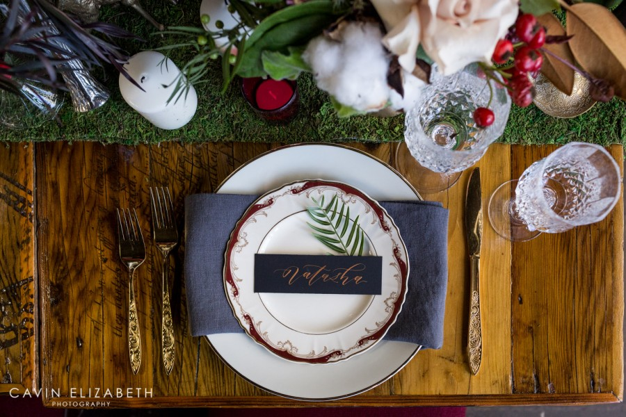 Marsala vintage wedding china with grey linen napkins and a black and copper place card, moss table runner with cotton and candles