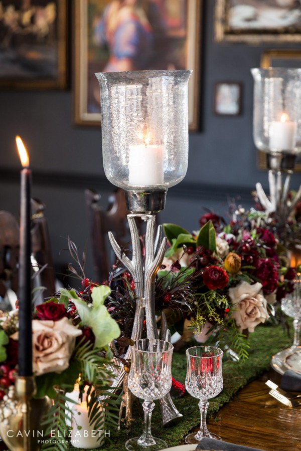Silver antler candle sticks, Dark and moody wedding inspiration at Lion's Share in San Diego, Blooms by Breesa Lee white green and red floral arrangement, black candles on a moss table runner