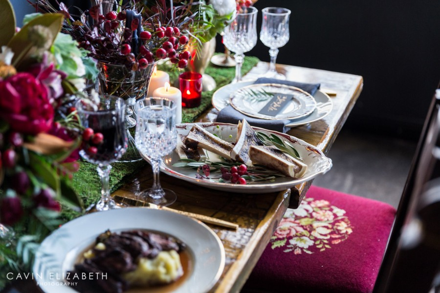 Hannibal inspired wedding with bone meat dishes and a moss table runner with red berries at The Lion's Share
