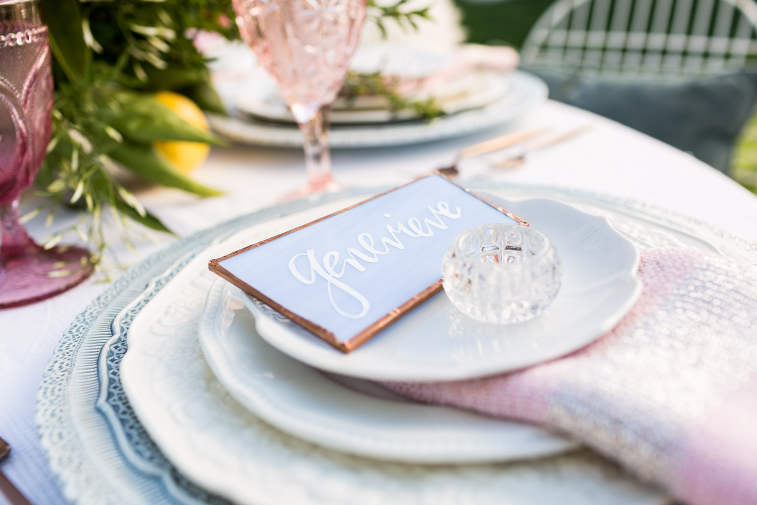 Calligraphy place cards for a wedding reception on blue serenity with a copper border