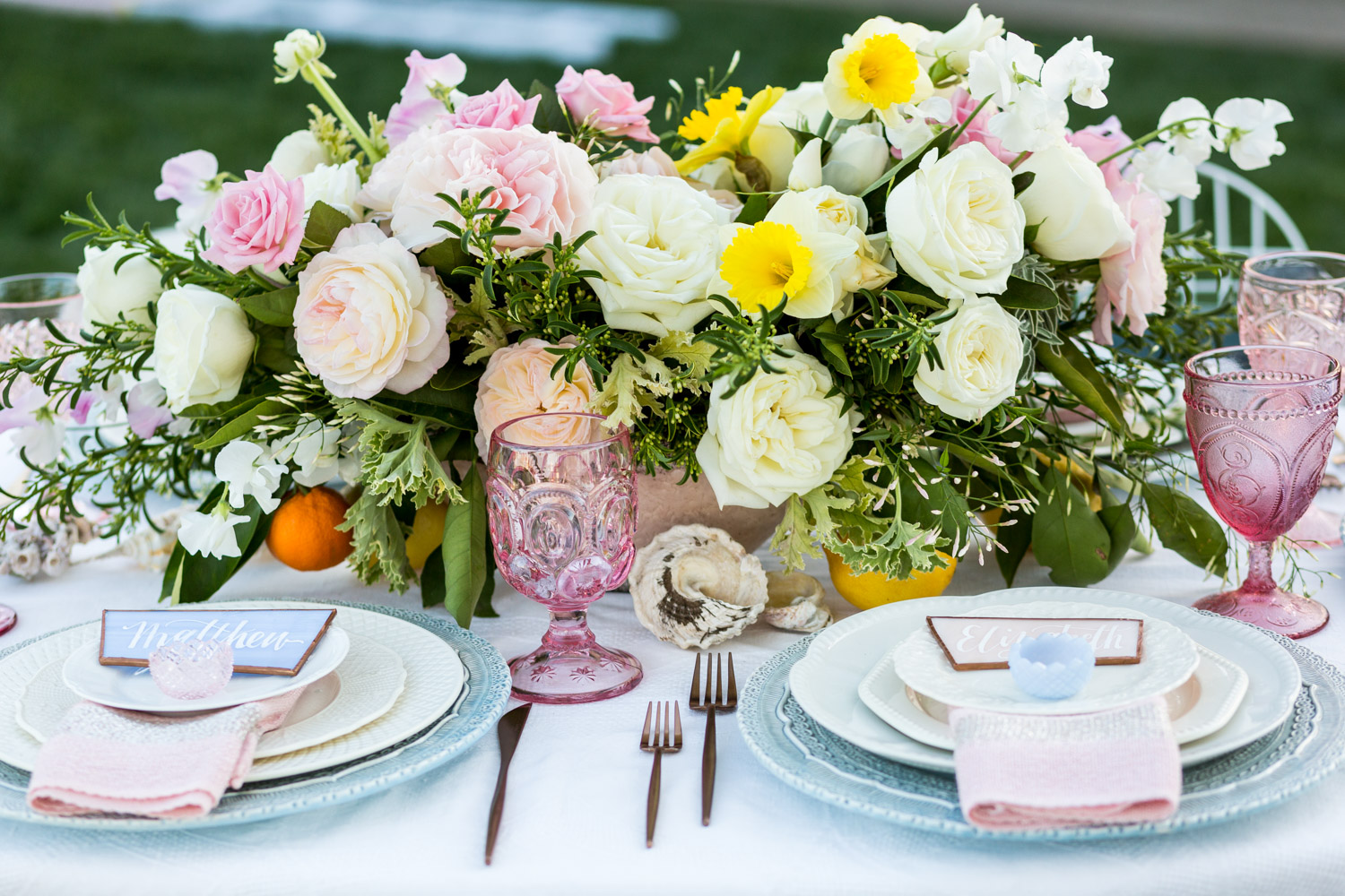 Wedding reception floral design arrangement with white and pink roses greenery and yellow daffodils