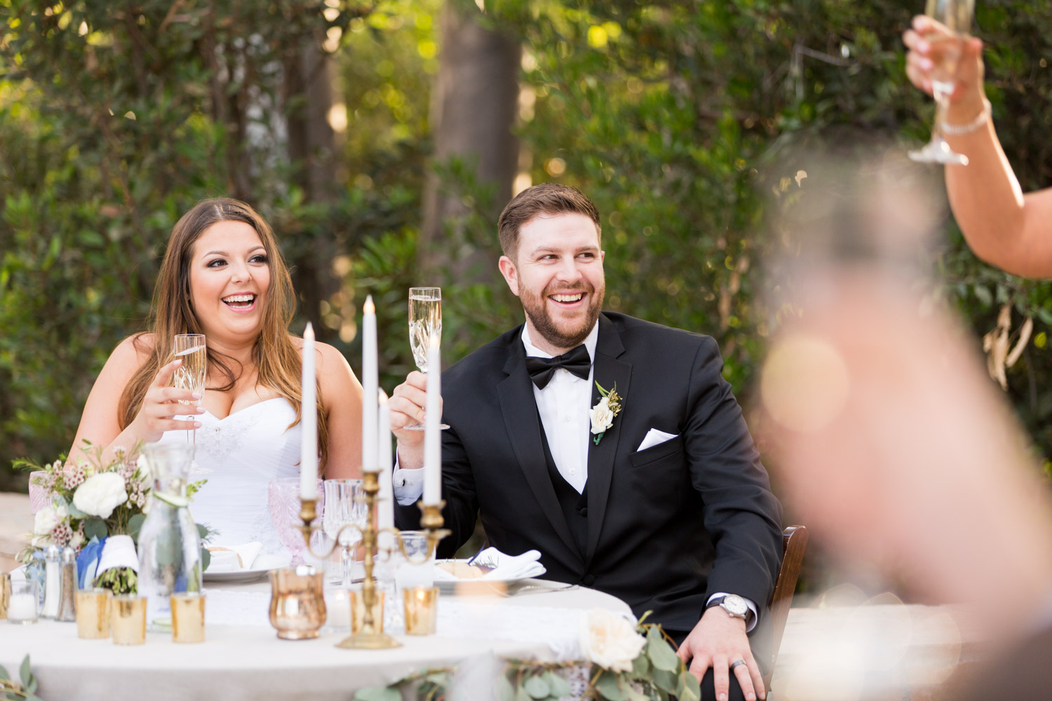 Beautiful candid wedding photography in San Diego during a toast, bride and groom laughing during toasts