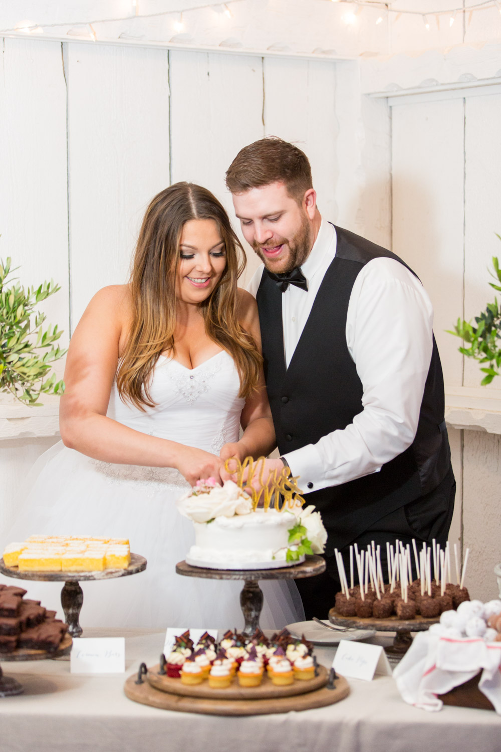 Cake cutting at Leo Carrillo Ranch, bride and groom cutting into a one tier white cake