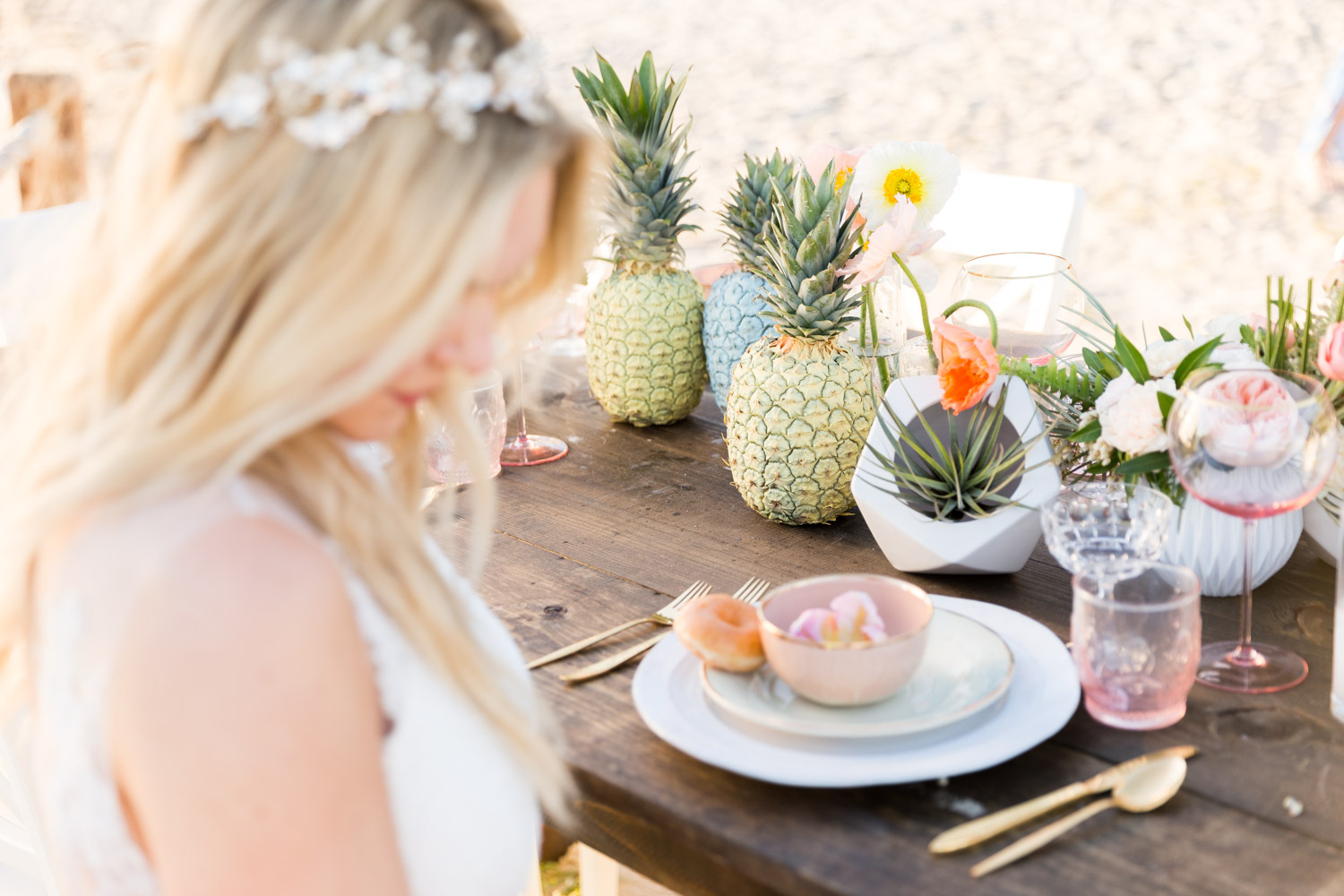 Tropical private estate wedding in San Diego by Couture Events, Air plants and pink and white flowers on a dark farm table with pineapples, bride at her Paradise Shores wedding reception