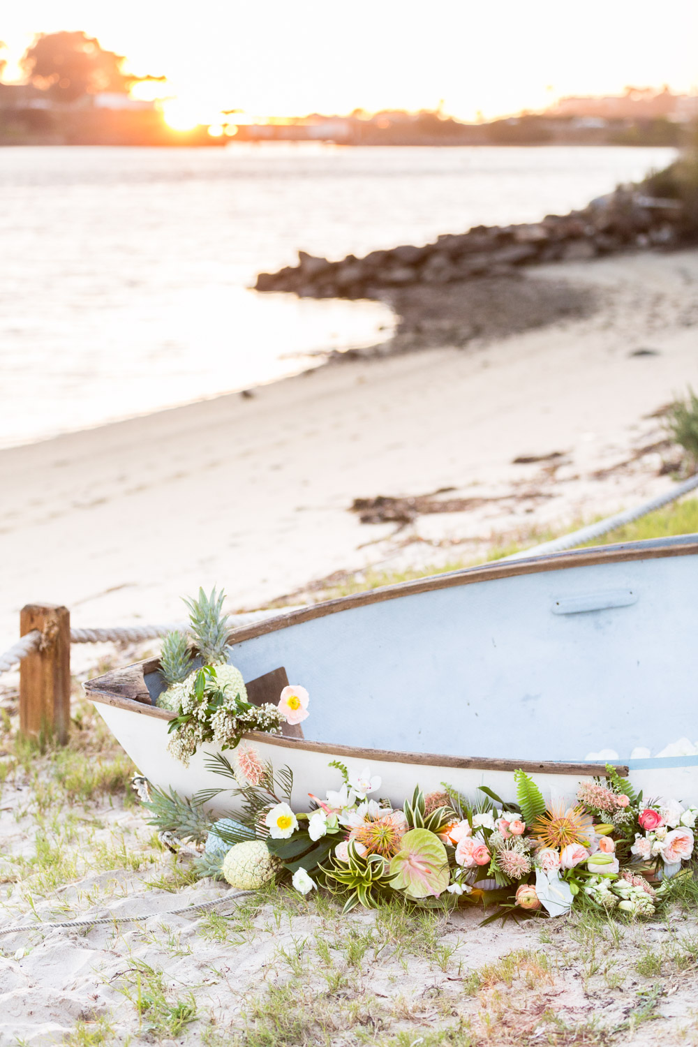 Luxury private estate wedding decor boat with flowers for a tropical themed wedding