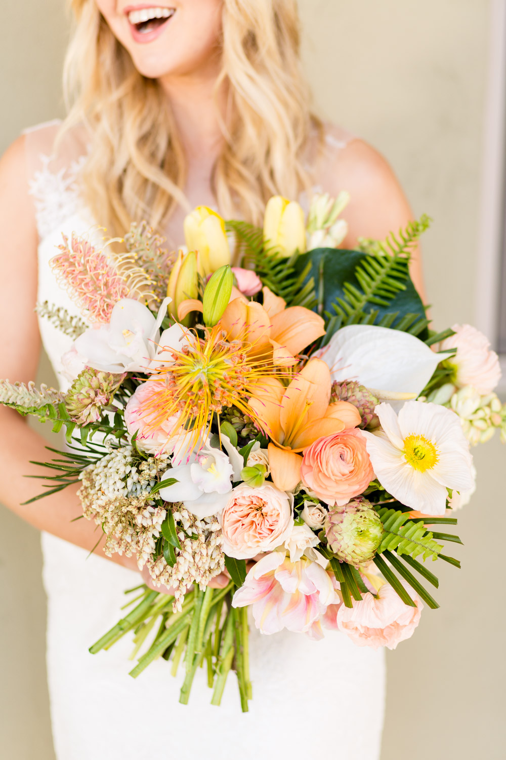 Large tropical bridal bouquet with pink orange white and green flowers and palm leaves by Leaf it to Lexi
