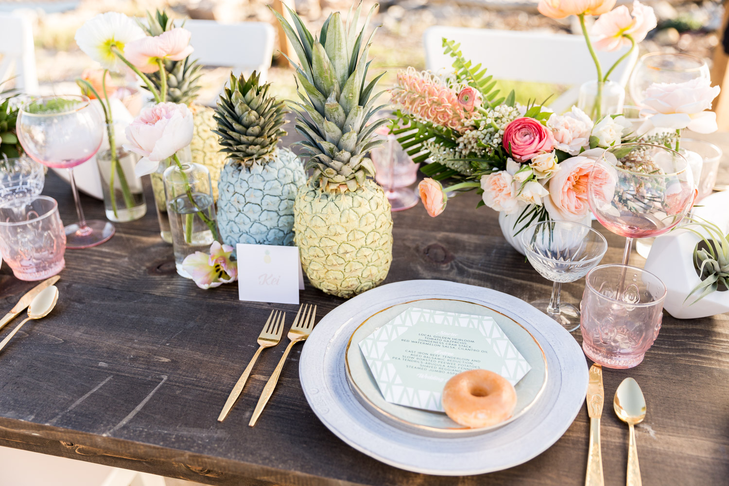 Tropical private estate wedding in San Diego by Couture Events, Air plants and pink and white flowers on a dark farm table with pineapples