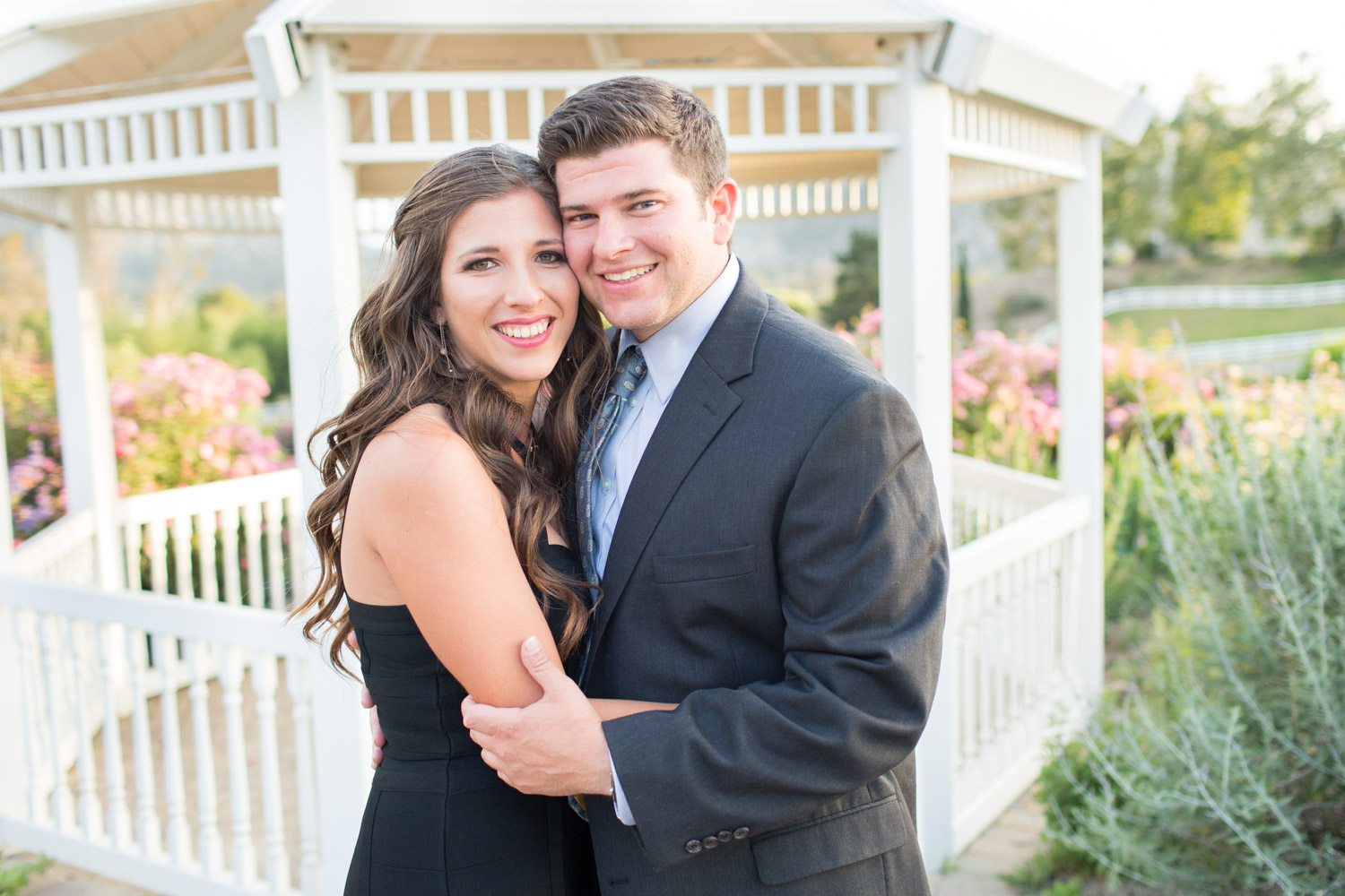 Black dress engagement photos -  Couple By A Gazebo Wearing A Black Dress And A Suit Rose Haven Heritage Garden