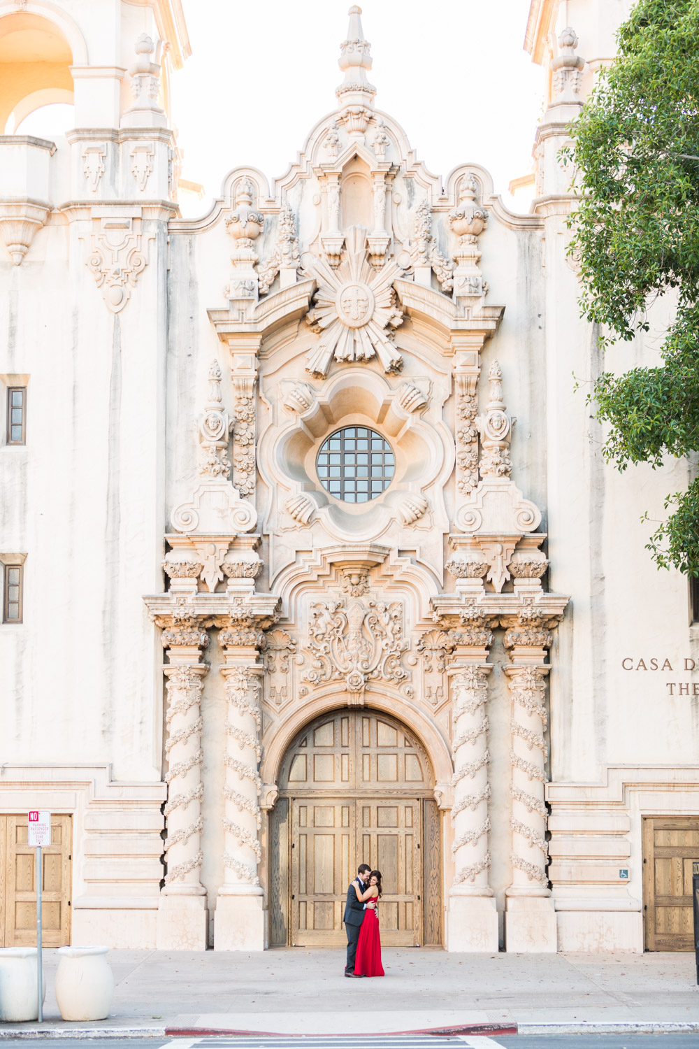 Formal engagement outfit for a session in Balboa Park, bride in a red Halston gown and groom in a suit and tie for their engagement photos, Balboa Park architecture, Cavin Elizabeth Photography