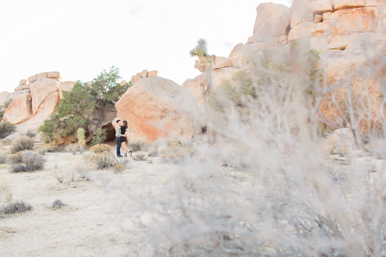 Engagement photos taken at Joshua Tree, wide shot of a couple on rocks at Joshua Tree, Cavin Elizabeth Photography