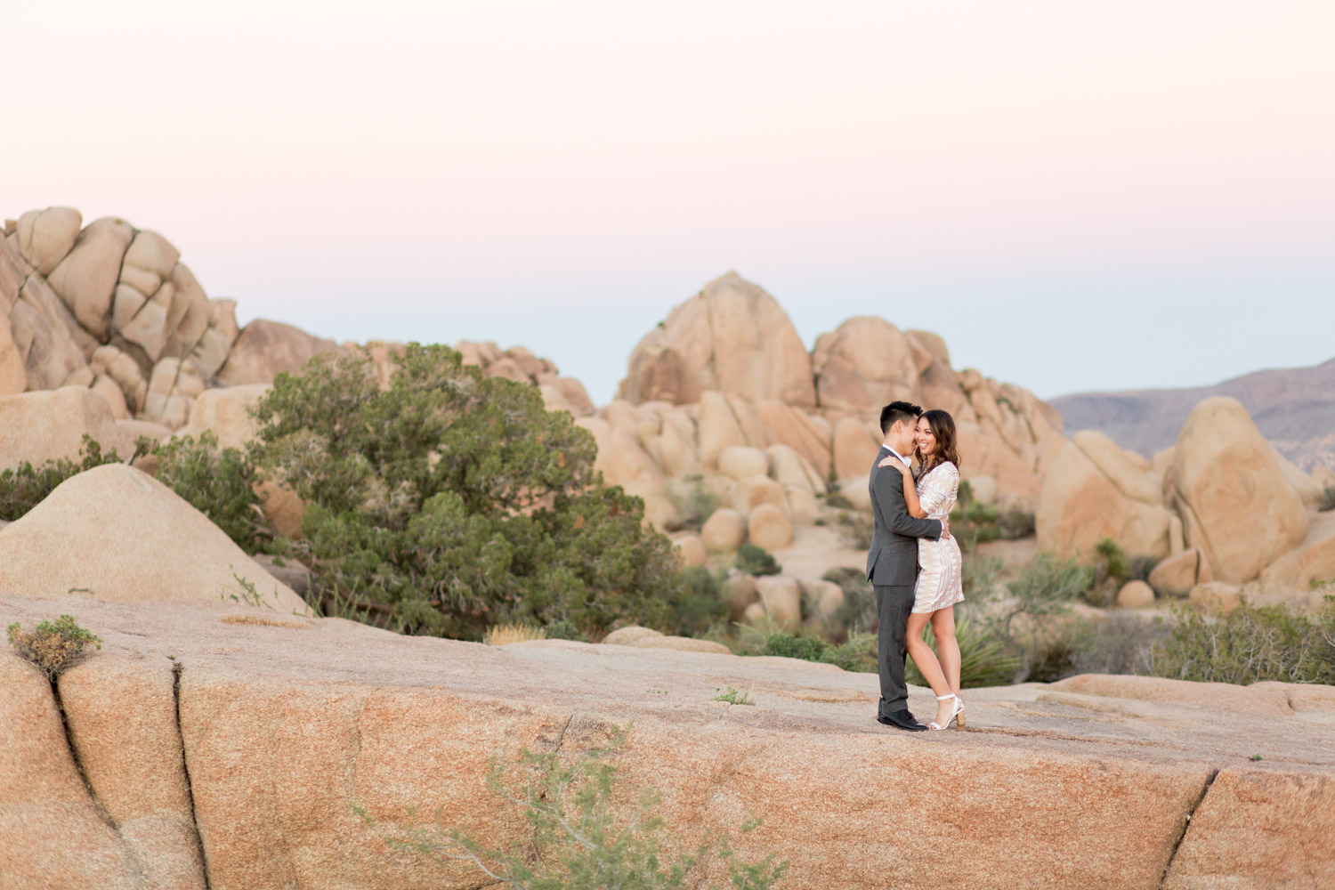 Engagement photo of a couple with Sunset at Joshua Tree surrounded by rocks, Cavin Elizabeth Photography