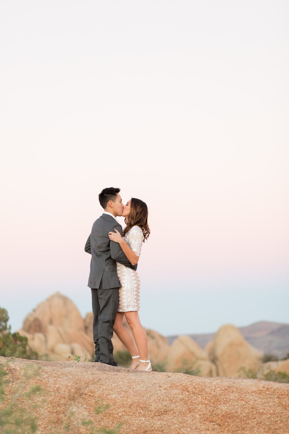 Kissing engagement photo of a couple with Sunset at Joshua Tree surrounded by rocks, Cavin Elizabeth Photography