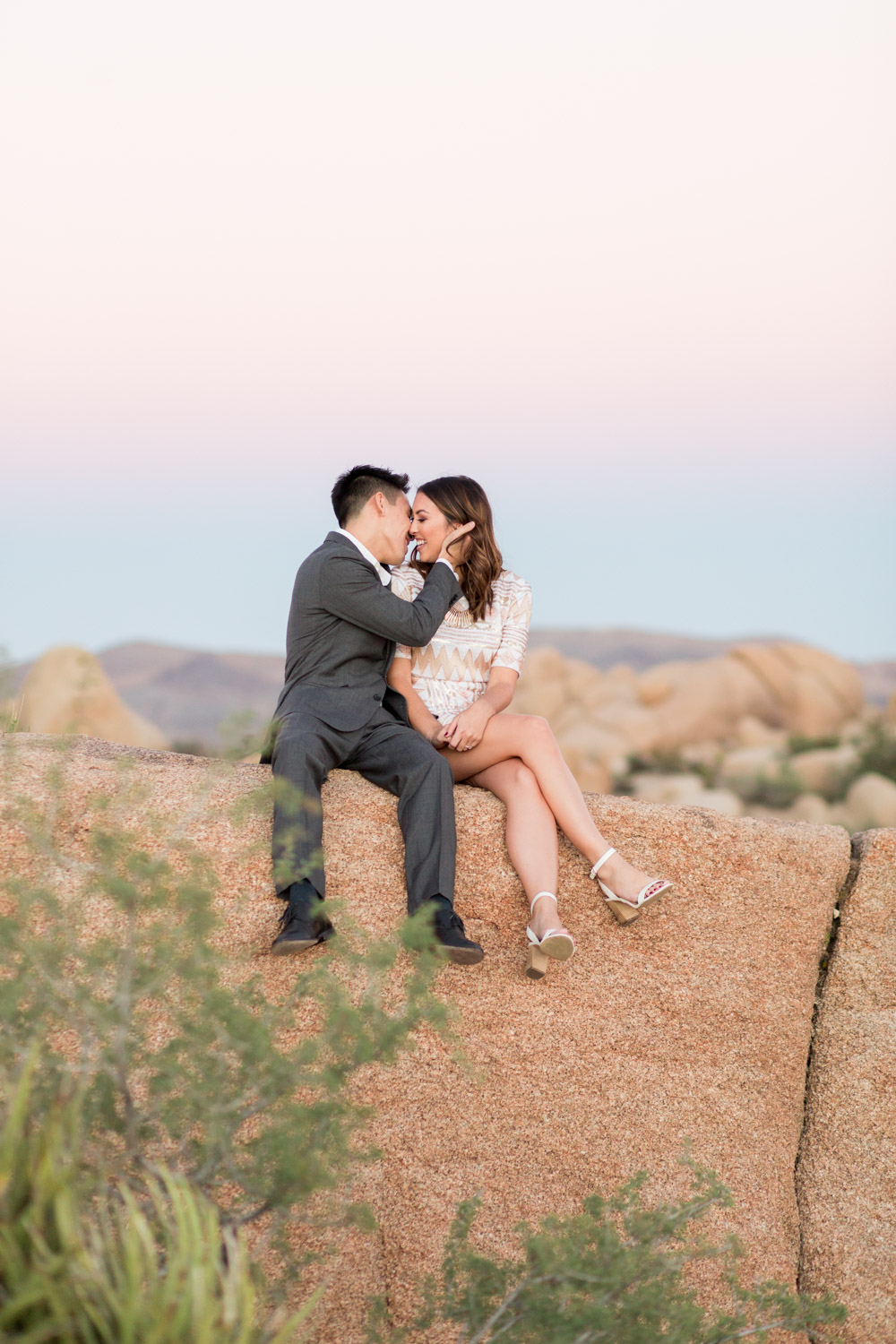 Intimate engagement photo of a couple with Sunset at Joshua Tree surrounded by rocks, Cavin Elizabeth Photography