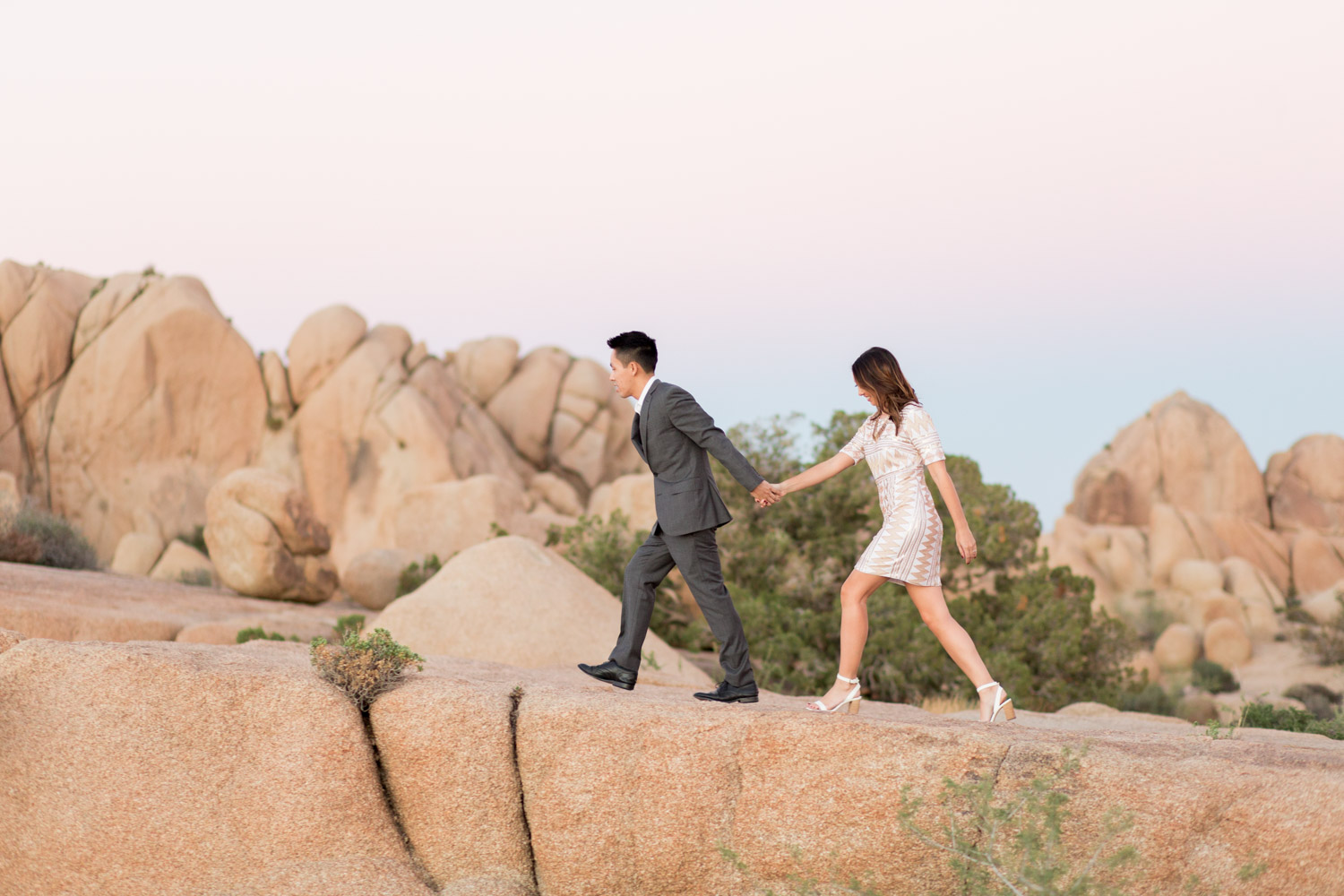 Couple walking, Engagement photo of a couple with Sunset at Joshua Tree surrounded by rocks, Cavin Elizabeth Photography