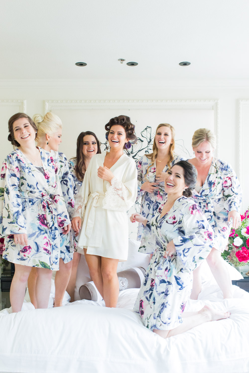 Bride and bridesmaids jumping on the bed in their robes, Cavin Elizabeth Photography