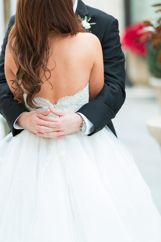 Groom hugging the bride in her Lazaro gown, Cavin Elizabeth Photography