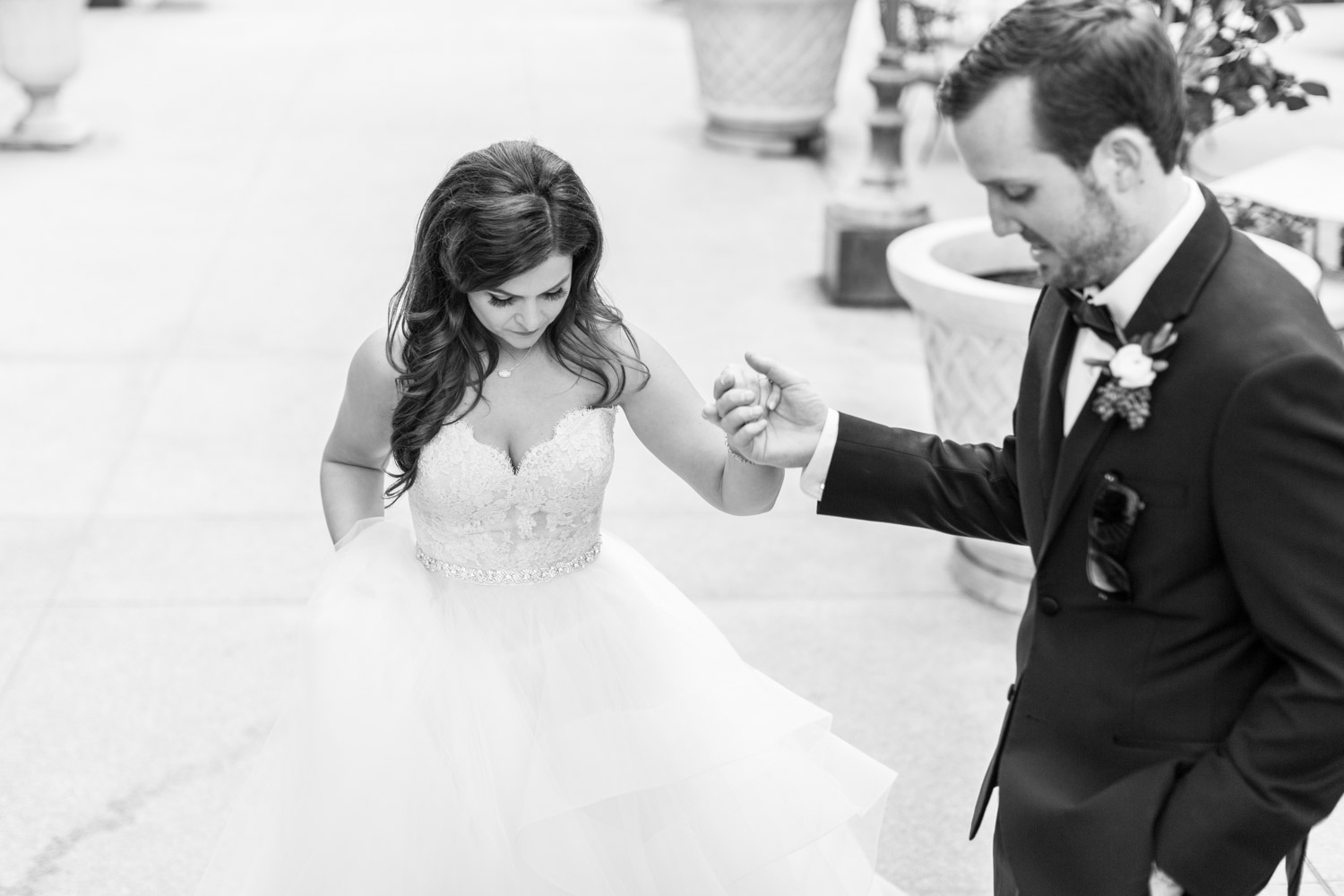 Groom helping bride up the stairs, Adorable candid wedding photography in black and white, Cavin Elizabeth Photography