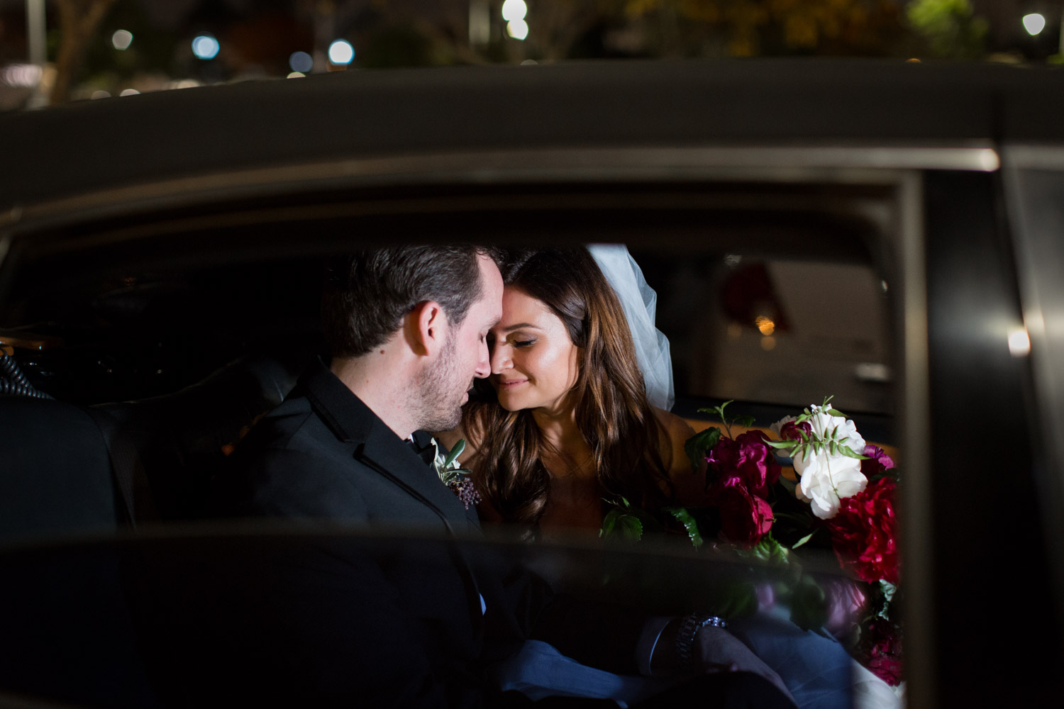 Bride and groom in a limo with dramatic light, Cavin ELizabeth Photography