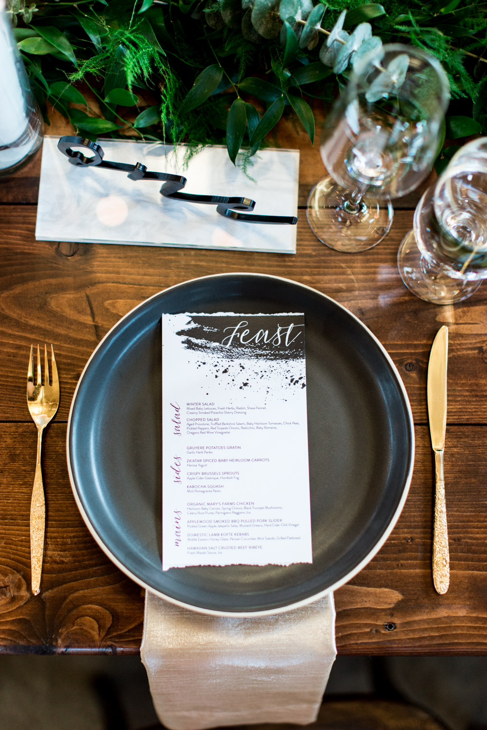 Black modern wedding charger with chic black brush stroke splattered menu, gold flatware, and acrylic black table number on marble, Cavin Elizabeth Photography