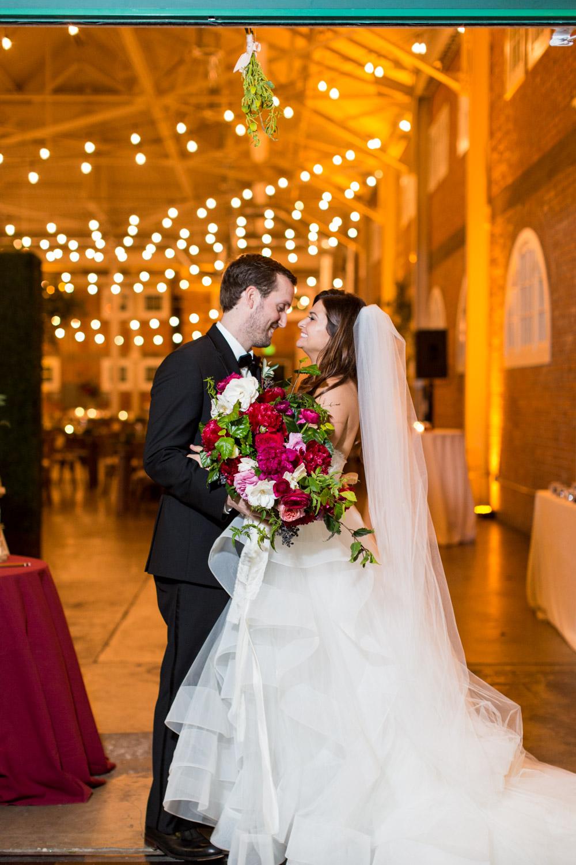Bride and groom at their BRICK wedding under the mistletoe, Cavin Elizabeth Photography