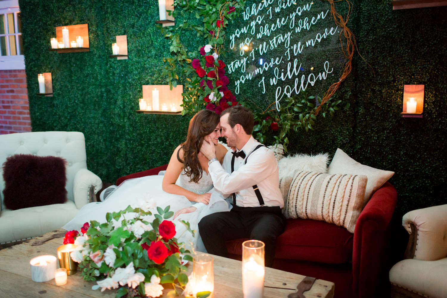 Bride and groom in wedding lounge with greenery wall backdrop and candles, Cavin ELizabeth Photography