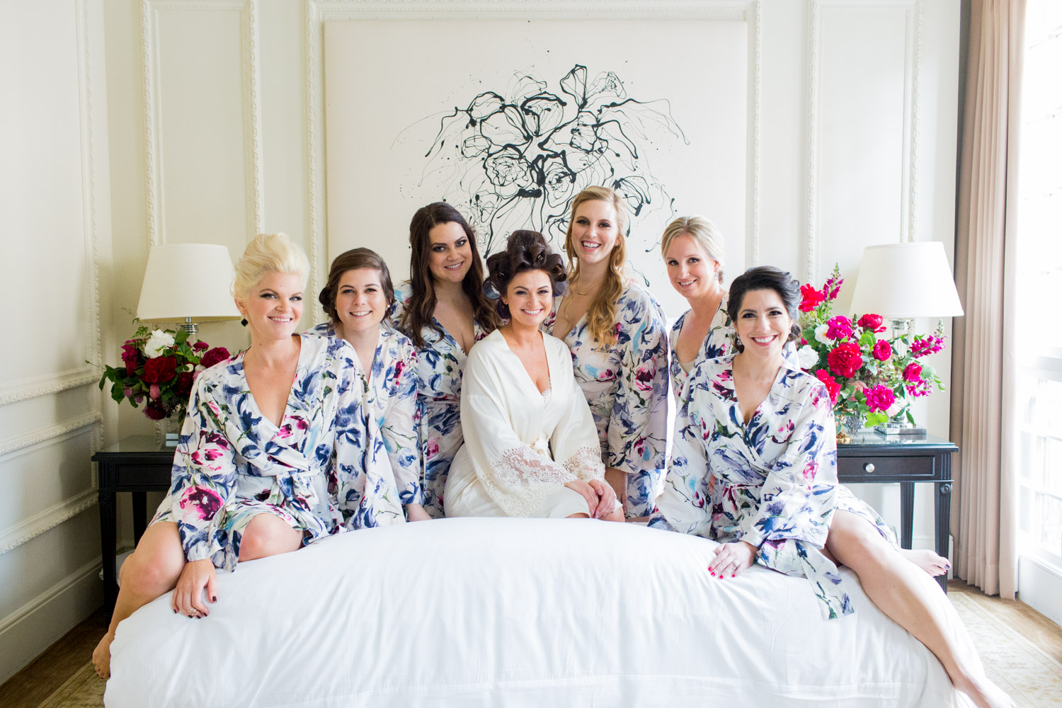 Bride and bridesmaids in robes on the bed, Cavin Elizabeth Photography