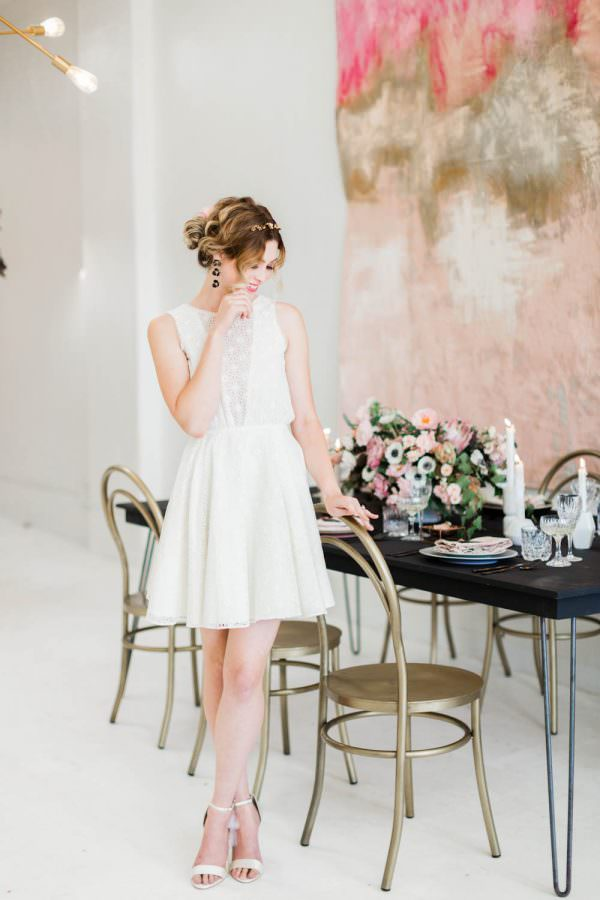 Bride dresses for her rehearsal dinner in a white eyelet mini dress with gold headpiece and dangling black earrings, Cavin Elizabeth Photography