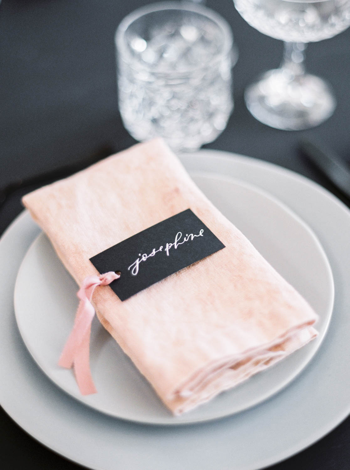 San Diego wedding film photographer, Pink napkin with black escort card with white calligraphy on grey plates, Cavin Elizabeth Photography