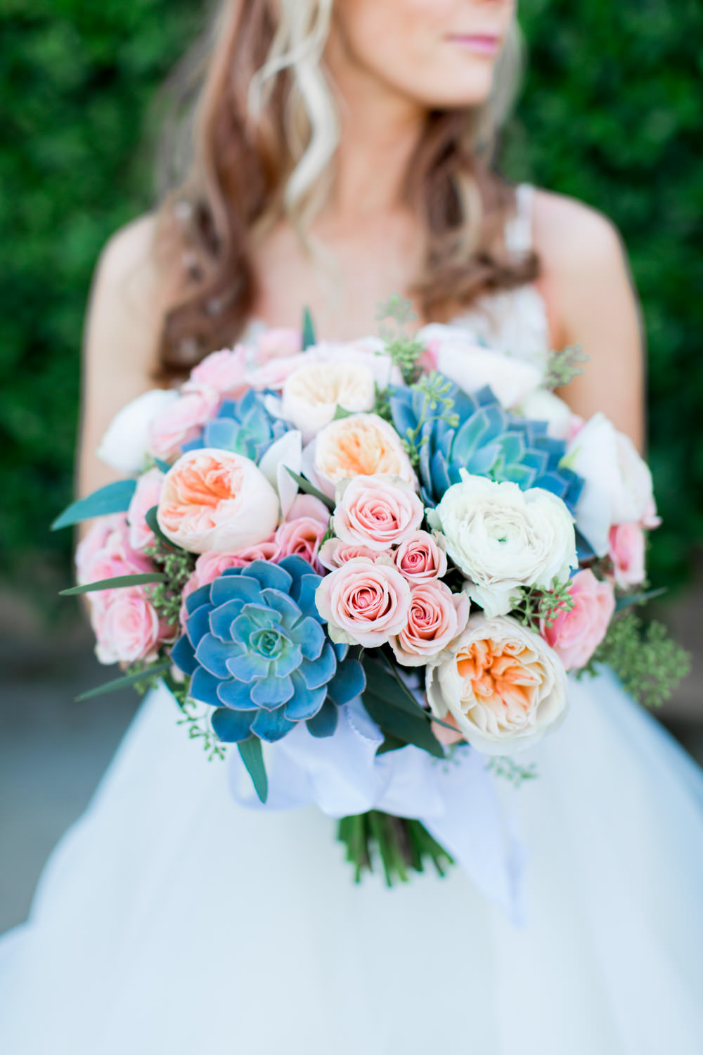 Succulent and pink bridal bouquet, Indian Wells wedding first look in front of a greenery wall and bride and groom portraits, Cavin Elizabeth Photography