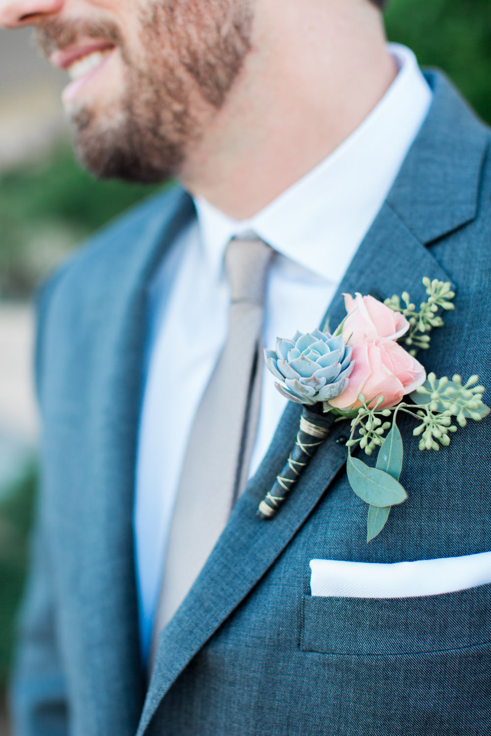 Succulent and pink boutonniere, Indian Wells wedding first look in front of a greenery wall and bride and groom portraits, Cavin Elizabeth Photography