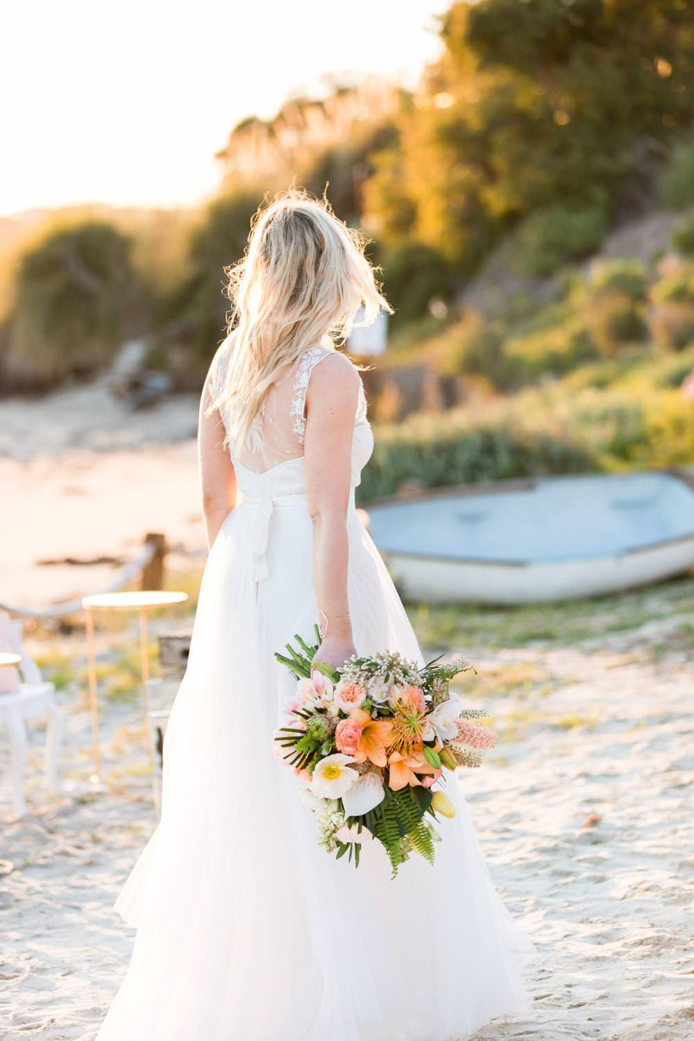 Bride carrying a tropical bridal bouquet by Leaf it to Lexi with palm leaves and pink white and orange flowers, flowy modern wedding gown from Elle BRidal Boutique, San Diego Wedding Dress Boutiques